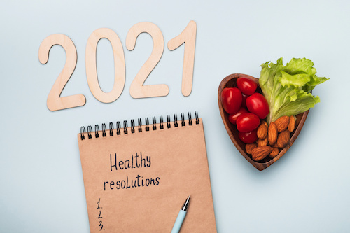 sign reading 2021 above a notepad with healthy resolutions and a numbered list