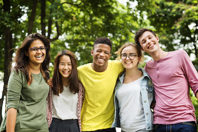 group image of multi-racial young adults standing outside in the woods