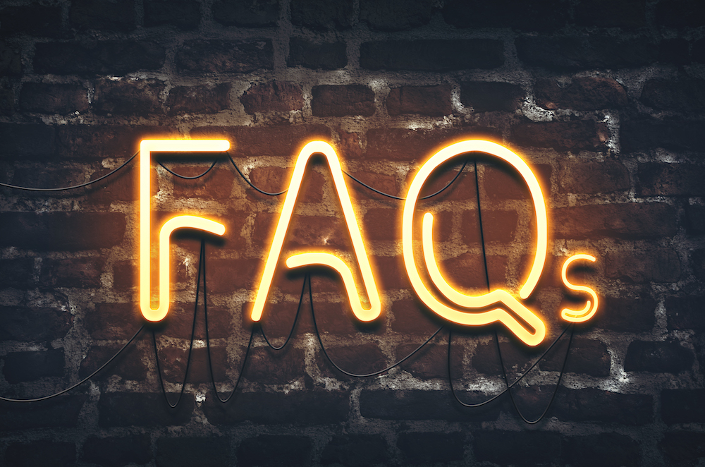 image of FAQs written in neon lights on a black brick wall